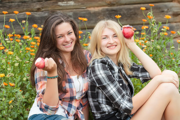Blonde and brunette posing with ripe apples