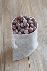 Hazelnuts in a linen bag on a wooden table.
