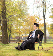 Graduate student holding diploma in park