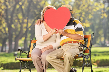 Mature couple kissing behind a red heart in a park