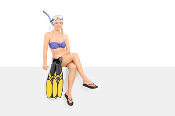Woman in bikini holding flippers seated on a panel