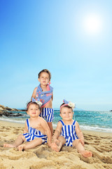 Three cute babies posing on a beach