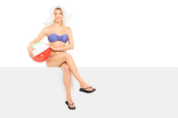Woman in bikini sitting on a panel and holding a beach ball