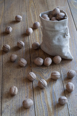 Walnuts in a canvas sack on wooden table.