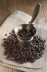 Coffee beans scattered on burlap around the mortar.