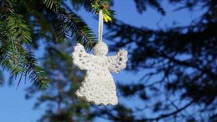 White Christmas Crochet Angel on spruce in forest