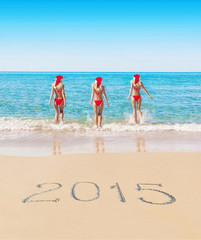 Womans in christmas hats on sea beach with caption 2015 on sand