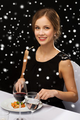 smiling woman with tablet pc eating main course