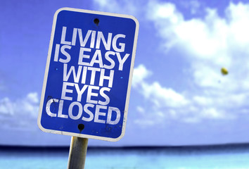 Living is Easy With Eyes Closed sign with a beach
