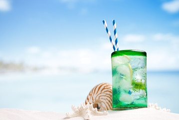 cocktail with ice, rum, lemon and mint   in a  glass  on beach