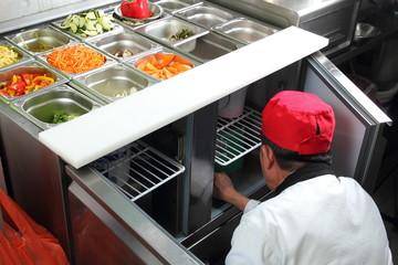 Asiatischer Koch vor Saladette