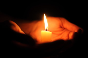 Candle on palms on a black background