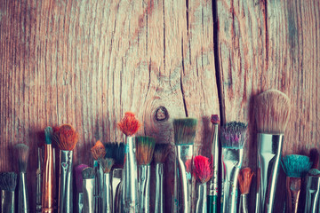 row of artist paintbrushes closeup on old wooden table, retro st