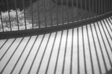 Infrared shot of metal railing throwing shadows on the pavement.