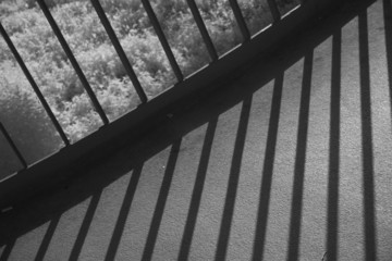 Infrared shot of metal railing throwing shadows on footbridge