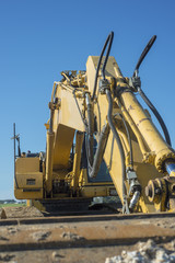 yellow excavator on blue sky background