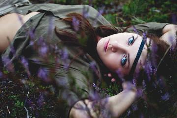A beautiful blue eyed woman laying down among purple heather