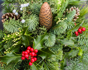 Mixed evergreen arrangement with pine cones and holly