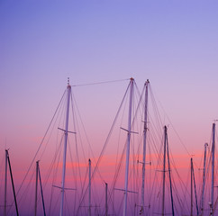 boat masts under a pink and orange sunset