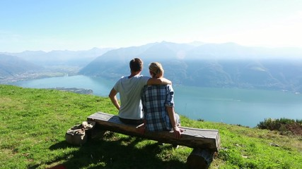 Young couple relaxing on bench, scenic view