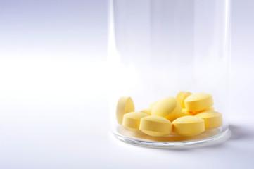 透明なビンに入った黄色い薬