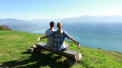 Young couple hugging on bench, scenic view