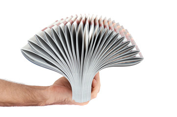 Pile of magazines in hand isolated over white