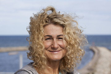 Portrait of smiling middle-aged woman. The sea in the background