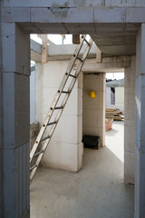Ladder and hard hat in rooms on a construction site