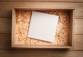 Empty wooden box with blank paper