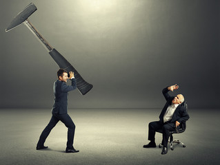 stressed young businessman holding big hammer
