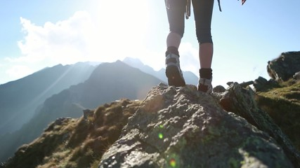 Hiker walks along narrow summit ridge crest, arms outstretch