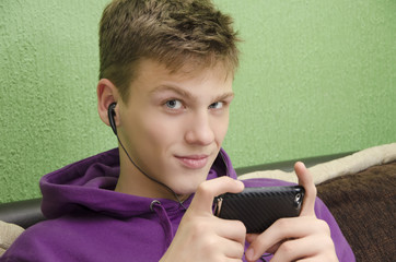 Beautiful blue-eyed teenager listening to music on smart phone