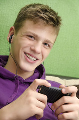 Happy teenager listening to music on smart phone via ear buds
