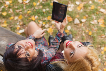 Two young woman holding a tablet in hand. Selective focus