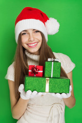 Beautiful teenage girl with Christmas hat and gift boxes smiling