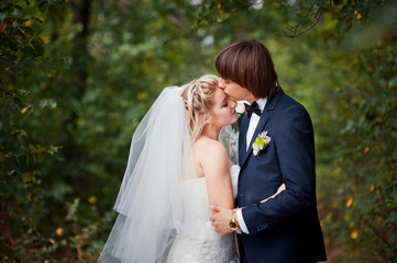 The groom kisses the bride at a wedding in the woods