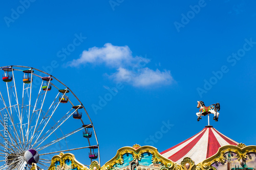 antique carousel horses tent and ferris wheel in amusement park - 72957334