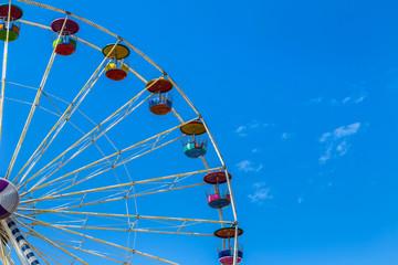 big colourful ferris wheel on blue sky background