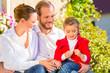 Familie sitzt im Garten vor Haus auf Bank in Sonne