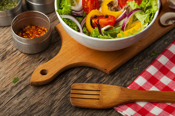 Fresh healthy salad on wooden table and kitchen utensil. View fr