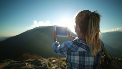 Tourist at top of mountain taking picture with digital tablet