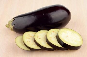 Studio shot single wet aubergine eggplant on wooden table
