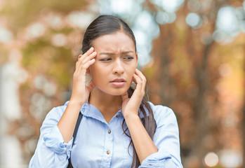 Stressed upset woman standing in park having headache