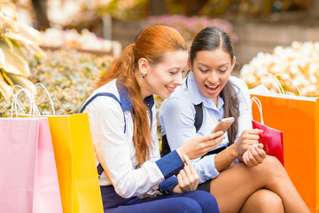 two surprised girls looking at cell phone discuss latest gossip