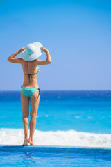 Young woman standing from back in sea with hat