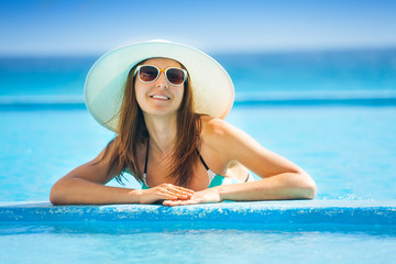 Happy woman wearing sunglasses with white hat