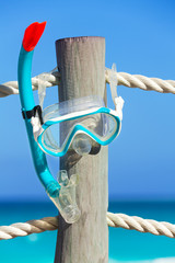 Snorkeling mask on wooden pier stake with ropes