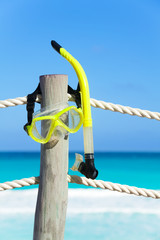 Yellow snorkeling mask hanging on the wooden stake