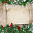 Christmas fir-tree with greeting card on wooden board